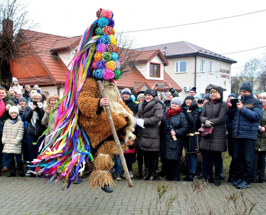 Brodacze, przebierańcy, siła tradycji w Sławatyczach, postaci przebrani w długie płaszcze, kolorowe kapelusze z bibuły, dugie brody.