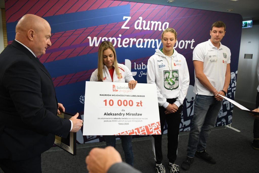 Marszałek przekazuje zawodnikowi okolicznościowy czek
